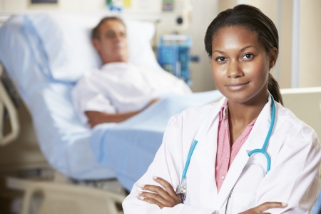 patient in bed: Portrait Of Doctor With Patient In Background Stock Photo