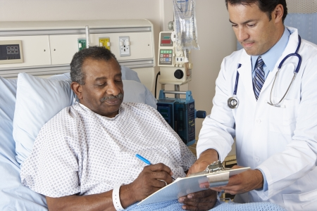 consent: Doctor Explaining Consent Form To Senior Patient
