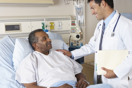 recovery bed: Doctor Visiting Senior Male Patient On Ward Stock Photo