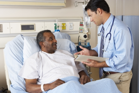 Doctor Visiting Senior Male Patient On Ward photo