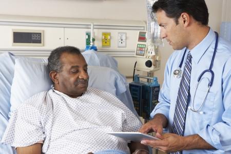 paciente: M�dico que usa la tableta digital en consulta con el paciente mayor Foto de archivo