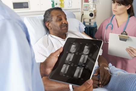 nurse and patient: Doctor Using Digital Tablet In Consultation With Senior Patient Stock Photo