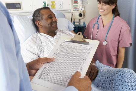 Doctor Looking At Chart With Senior Male Patient photo