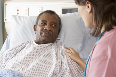 black nurse: Nurse Talking To Senior Male Patient On Ward
