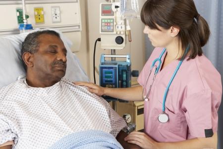 sick person: Enfermera controla al paciente mayor de hombre a la sala