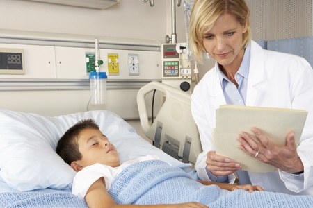 Doctor Visiting Child Patient On Ward photo