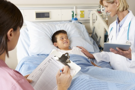 pediatric nurse: Doctor Using Digital Notepad Whilst Visiting Child Patient