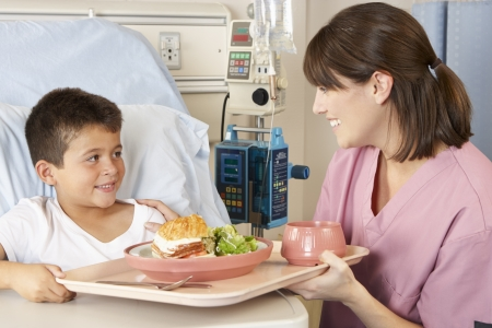 Enfermera Servir comidas Ni�o paciente en cama de hospital photo