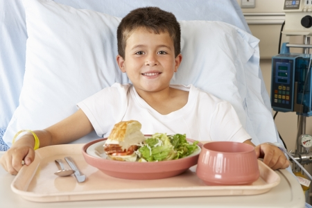Boy Eating Meal In Hospital Bed photo