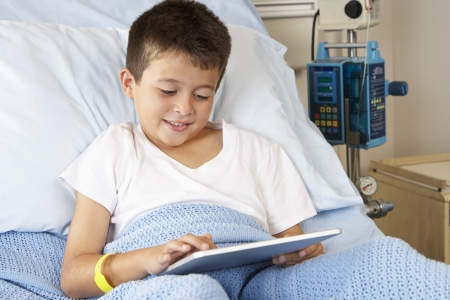 child in bed: Boy Relaxing In Hospital Bed With Digital Tablet Stock Photo