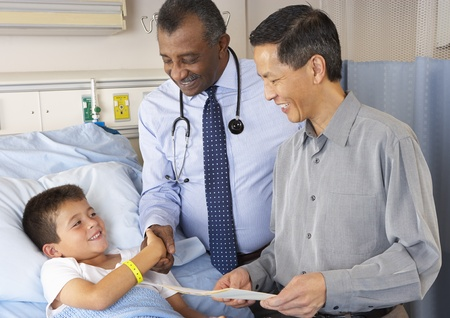 hospital notes: Doctors Visiting Child Patient On Ward Stock Photo