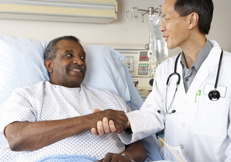 hospital notes: Doctor Visiting Senior Male Patient On Ward Stock Photo