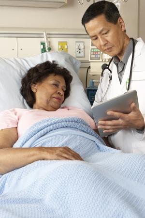 recovery bed: Medico con tavoletta digitale Talking With paziente anziano