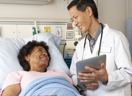 patient bed: Doctor Using Digital Tablet Talking With Senior Patient