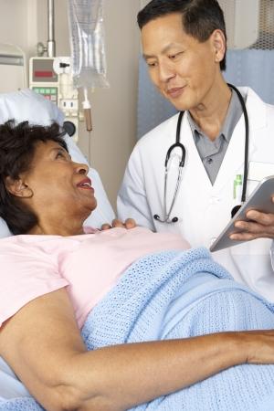 asian nurse: Doctor Using Digital Tablet Talking With Senior Patient