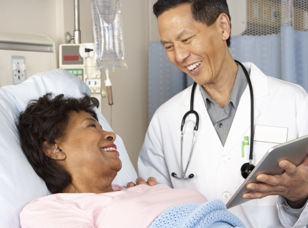 nurse computer: Doctor Using Digital Tablet Talking With Senior Patient