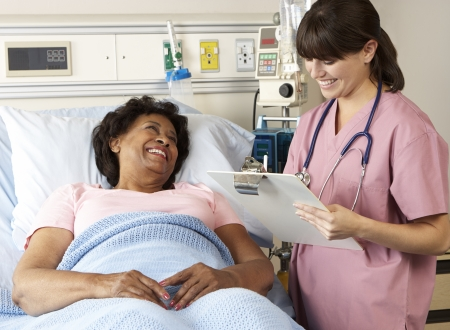patient in bed: Nurse Visiting Senior Female Patient On Ward