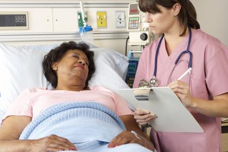 recovery bed: Infermiera Visiting senior femminile del paziente Ward Archivio Fotografico