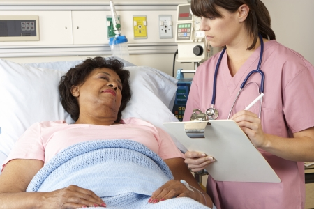 Nurse Visiting Senior Female Patient On Ward photo