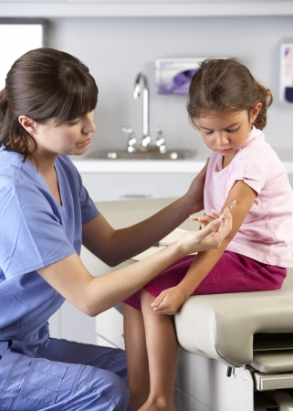 Doctor Giving Child Injection In Doctors Office photo