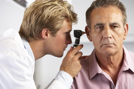 otoscope: Doctor Examining Male Patients Ears Stock Photo