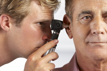 doctor's appointment: Doctor Examining Male Patients Ears Stock Photo
