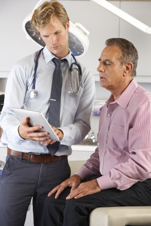 check up: Doctor Discussing Records With Patient Using Digital Tablet