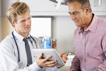 appointment: Doctor Discussing Records With Patient Using Digital Tablet