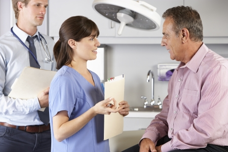 Male Patient Being Examined By Doctor And Intern Stock Photo - 18735955