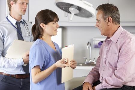 enfermera con paciente: Paciente masculino siendo examinado por el doctor y el interno
