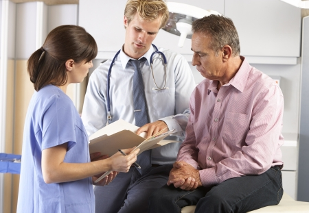 Male Patient Being Examined By Doctor And Intern photo
