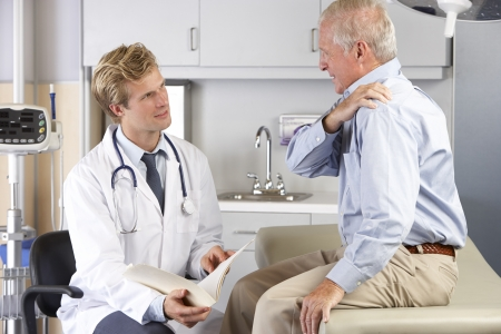 senior pain: Doctor Examining Male Patient With Shoulder Pain Stock Photo