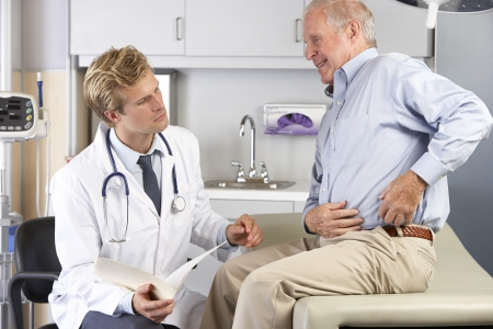 Doctor Examining Male Patient With Hip Pain photo