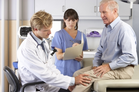 senior pain: Doctor Examining Male Patient With Knee Pain Stock Photo