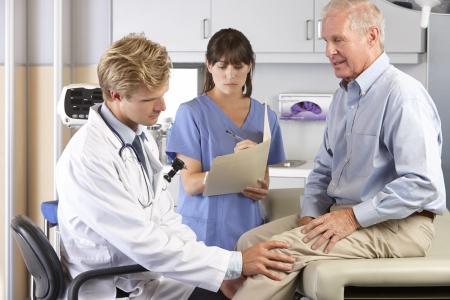 elderly pain: Medico esame paziente maschio con dolore del ginocchio