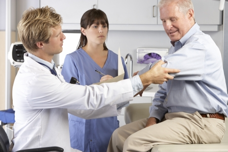 senior pain: Doctor Examining Male Patient With Elbow Pain