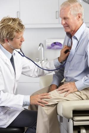 dolor de pecho: Médico ausculta el pecho del paciente Masculino