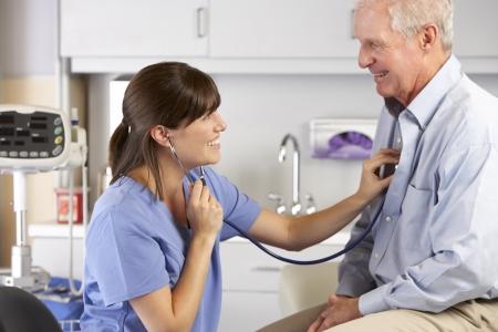 dolor de pecho: M�dico ausculta el pecho del paciente Masculino