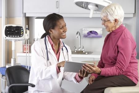 Médico Discutir registros con el paciente femenino senior