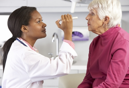 Doctor Examining Senior Female Patient's Eyes photo