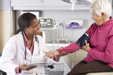 doctor examining woman: Doctor Taking Senior Female Patients Blood Pressure
