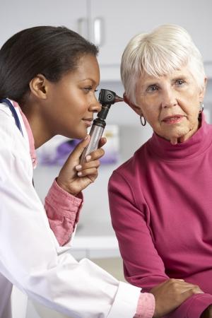 otoscope: Doctor Examining Senior Female Patients Ears