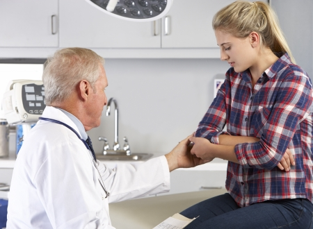 check up: Teenage Girl Visits Doctors Office With Elbow Pain Stock Photo