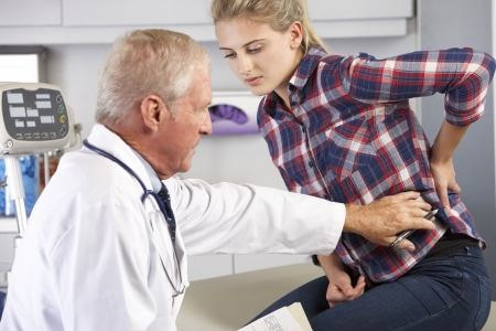 back ache: Teenage Girl Visits Doctors Office With Back Pain Stock Photo
