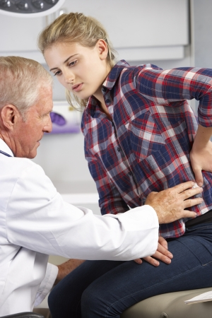 17 year old: Teenage Girl Visits Doctors Office With Back Pain Stock Photo