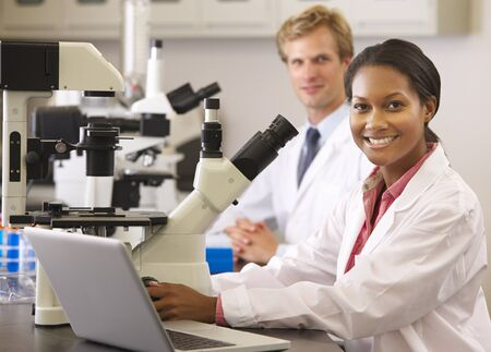 scientist woman: Male And Female Scientists Using Microscopes In Laboratory