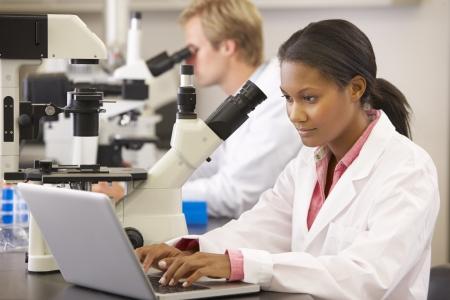 cientificos: Cient�ficos y las cient�ficas Usando microscopios en laboratorio Foto de archivo