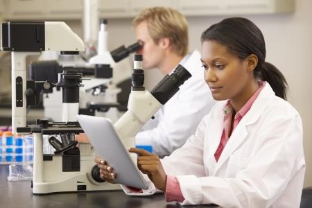 lab coat: Gli scienziati utilizzano i microscopi e la tavoletta digitale in laboratorio Archivio Fotografico