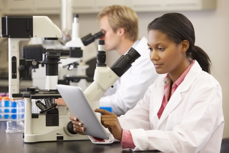 bata de laboratorio: Los científicos que usan microscopios y Tablet Digital En Laboratorio