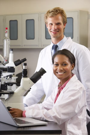 lab coat: Male And Female Scientists Using Microscopes In Laboratory